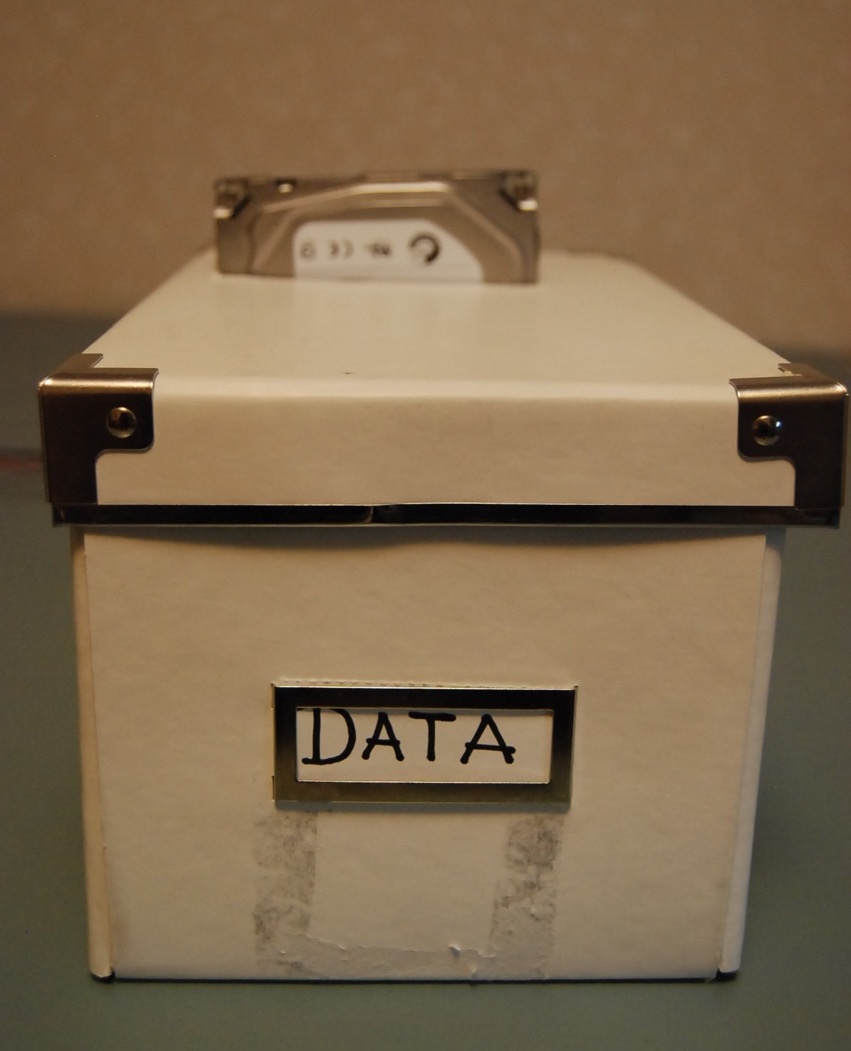 "IKEA Kassett box with HDD sticking out, labelled ""DATA"""